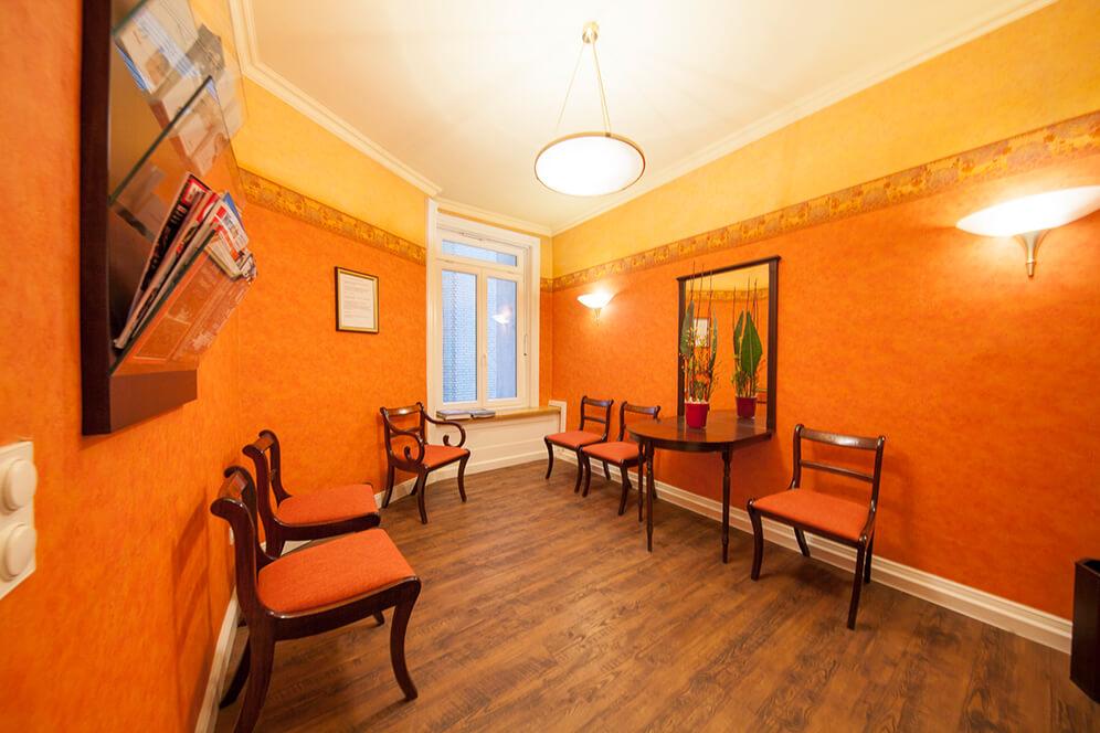 Warme Farben im Wartezimmer und bequeme Sitzmöglichkeiten in der Kieferorthopädie in Hamburg